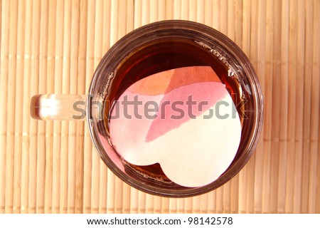 red paper heart gets wet and immersed in a transparent mug with black tea - the concept of love of suffering and tears
