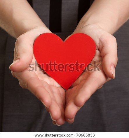 red paper heart on the hands
