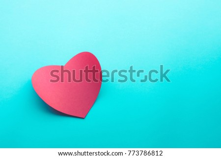 Red paper heart shape on blue background.love,