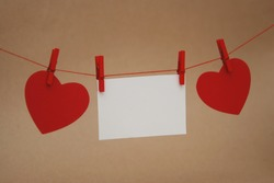 Red Paper Hearts Hanging on String with mini Clothes Pin over Ivory Neutral Background.