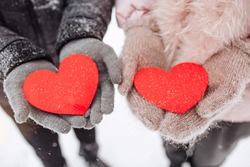 Red paper hearts in the hands of a loving couple outside at a snowy winter park. Romantic man and woman celebrate Valentine's day with symbols of love. Sign of 14 February