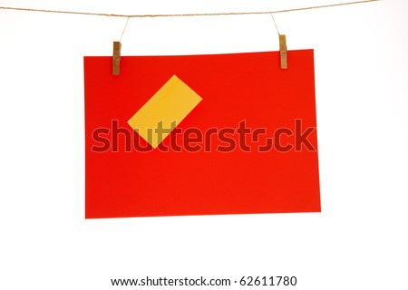 Red paper sheet and yellow on a clothes line. Isolated on white background.