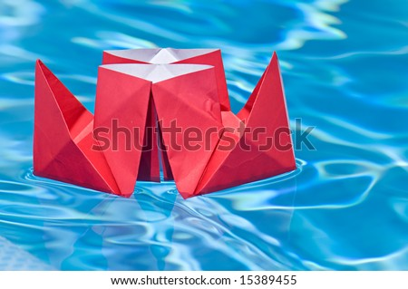 Red paper ship sailing on a blue water of a pool