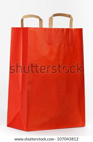 Red paper shopping bag on white.