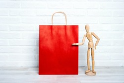 Red paper shopping bag with wooden dummy in a proposing pose on white brick wall background. Copy space for text. Shopping, sale, Black Friday concept.