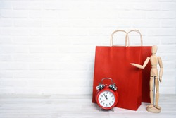 Red paper shopping bags with classic alarm clock and wooden dummy in a proposing pose on white brick wall background. Copy space for text. Shopping, sale, Black Friday concept.