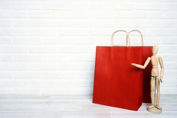 Red paper shopping bags with wooden dummy in a proposing pose on white brick wall background. Copy space for text. Shopping, sale, Black Friday concept.