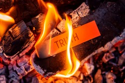 Red paper with inscription Truth burning in the fire. Hiding truth, telling a lie symbol