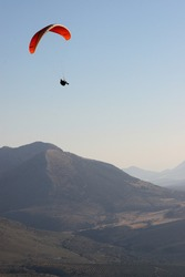 Red paraglider flying high in the afternoon in a mountain range of Andalusia.