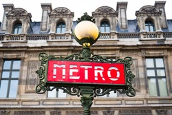 Red Paris metro subway entry sign fronting the Louvre Museum.