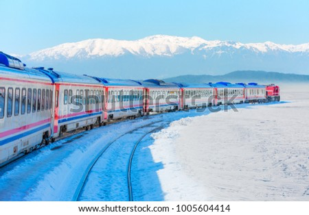Red passenger diesel train moving at the terminal. Snow covered railway tracks -  East express between Ankara and Kars - Turkey