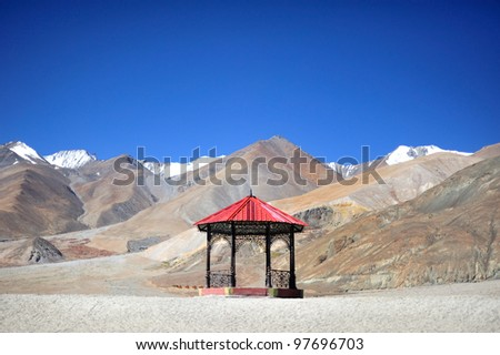Red pavilion alone in the middle of frame with snow mountain in background and clear blue sky at Pangong Lake, India - stock photo