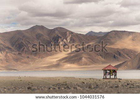 Red pavilion over Pangong Lake and Mountains. It is huge and highest lake and cloudy sky background in Ladakh, India located in the north Indian state of Jammu. Pangong Lake is one of Ladakh landmark.