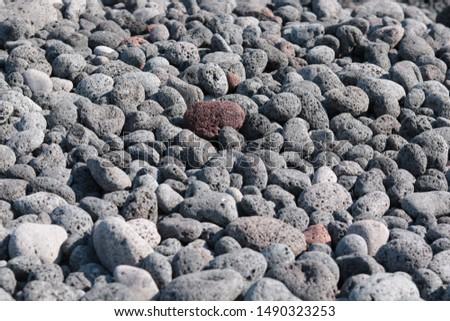 Red Pebble among grey pebbles