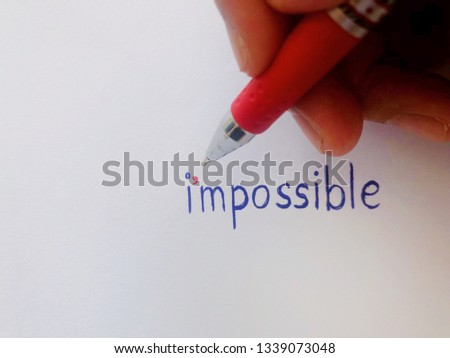 Red pen using to write apostrophe mark to change impossible word to I'm possible, inspiration quote for changing negative mind. White background concept wording. #1339073048