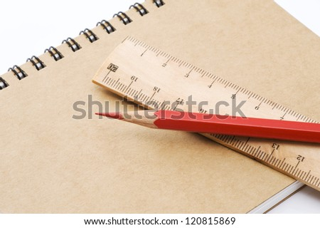 Red pencil and wooden ruler on closed notebook