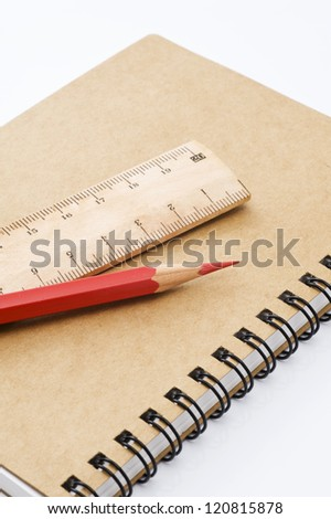 Red pencil and wooden ruler on closed notebook - stock photo