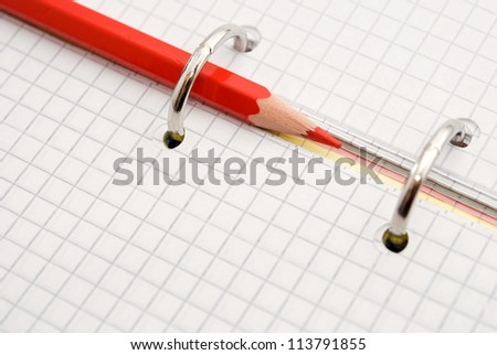 red pencil on notebook background