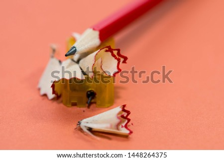 Red pencil on sharpening waste and plastic sharpener close up macro shot on light red background.
