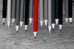 Red pencil stand out from the rest of the pencils in black and white. Focus at red color pencil.