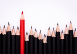 Red pencil standing out from black pencil fellows on white background, uniqueness, leadership, independence, think difference, find the way to the winner, business successfuly in life.
