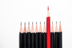 Red pencil standing out from crowd of identical black pencils on white background, be leader and unique, independence, initiative, strategy, the one think different, business success concept