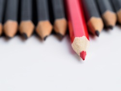 Red pencil standing out from crowd of plenty identical black fellows on white background. Leadership, uniqueness, independence think, initiative, strategy, dissent, business success concept