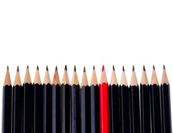 Red pencil standing out from crowd of plenty identical black fellows on white background. business success concept