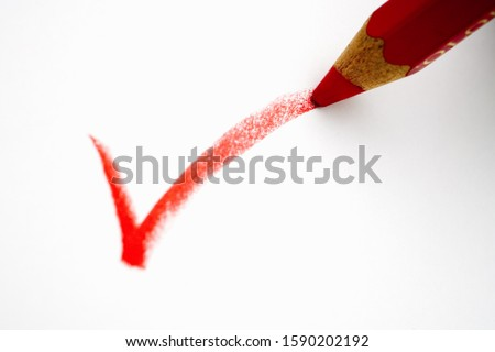 Red pencil writing a check mark