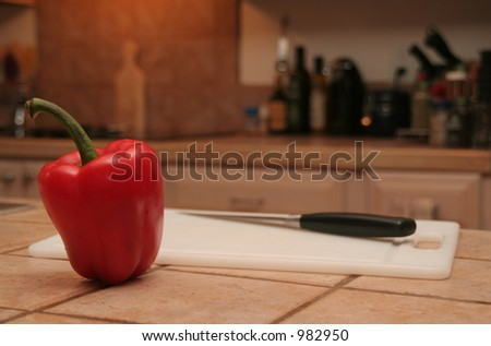 Red pepper next to cutting board blurred kitchen in background