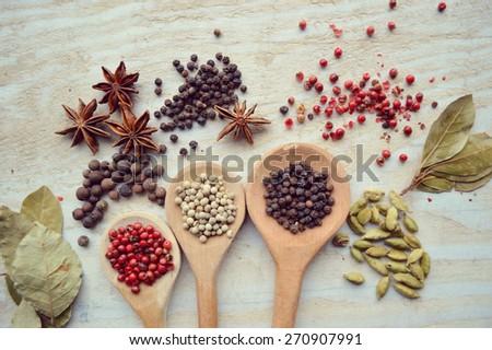 red pepper peas,black pepper peas,white pepper corns,a Bay leaf,cardamom on wooden background