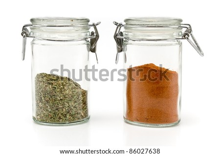 Red pepper powder and oregano in jars isolated on white
