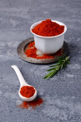 Red pepper powder on a gray slate background. The concept of cooking spices. Selective focus.