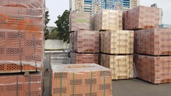 Red perforated bricks with rectangular holes on wooden pallets in an open-air warehouse ready for sale. New bricks on pallets at a hardware store.