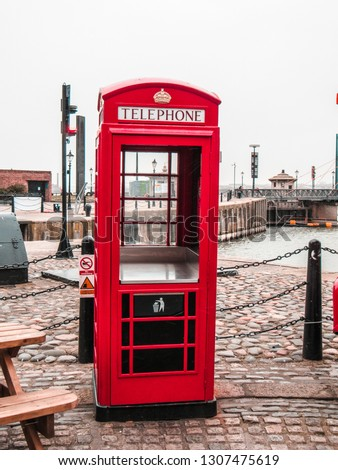 Red phone booth in Liverpool used for throwing trash. Vibrant colors. Grey sky with clouds showing a typical rainy day in England.  photo in England #1307475619