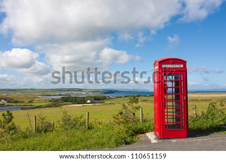Red phone booth in Northern Ireland with a backdrop of  cliffs and the atlantic ocean and a small village shot in landscape
