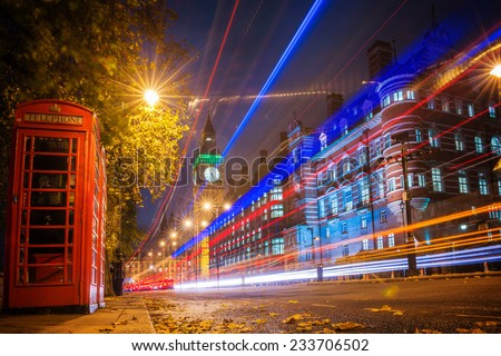 Red phone booth is one of the most famous of London icons with bus blur at night