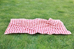 Red picnic blanket on green grass background,empty space gingham tablecloth outdoors food advertisement design.Easter decorative backdrop.