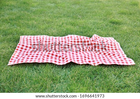 Red picnic blanket on green grass background,empty space gingham tablecloth outdoors food advertisement design.Easter decorative backdrop. Stockfoto ©