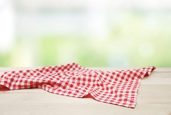 Red picnic cloth towel on wooden table natural blurred background,product display,food advertisement design.Gingham napkin.