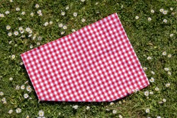 Red picnic tablecloth. Red checkered picnic blanket on a meadow with daisies in bloom. Beautiful backdrop for your product placement or montage. Topview.
