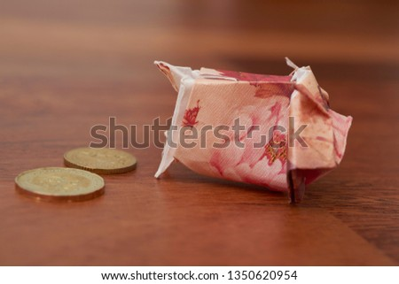 Red Piggy bank origami made using paper and a coin with blurry background. Concept shows saving, investment and banking. #1350620954