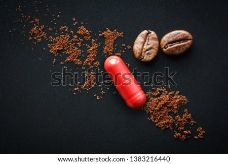 red pill and coffee beans on a black background, the concept of drugs containing caffeine