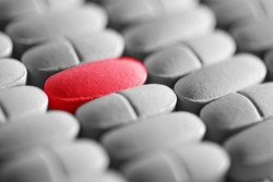 Red pill in row of monochrome pills. Macro image.