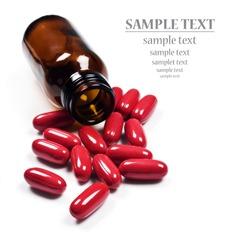 Red pills spilled around a pill bottle