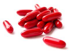 Red pills spilled on white background