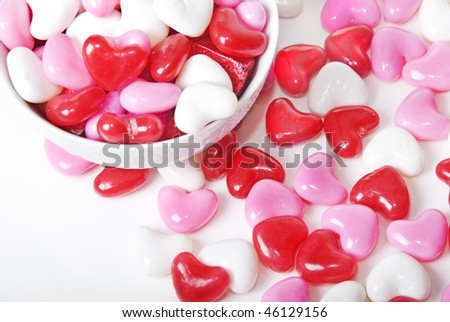 Red, pink and white heart shaped sweet scattered around a white bowl full of sweets
