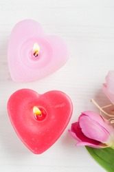 Red pink heart candles and tulips on a white shabby wooden background and empty space for text. Top view with copy space