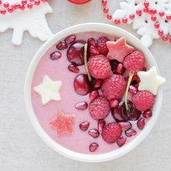 red pink smoothie bowl with cherry, strawberry, raspberries and pomegranate , christmas fun festive food