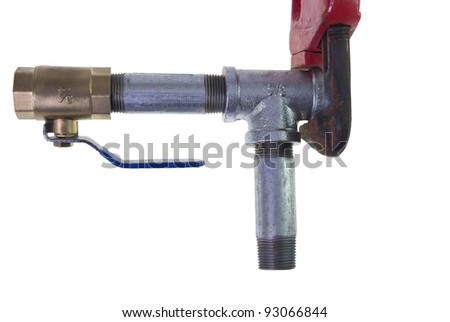 red pipe wrench gripping metal tee joint